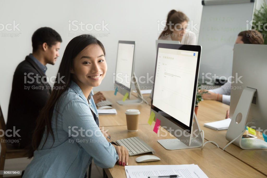 Smiling asian office employee looking at camera working with colleagues stock photo
