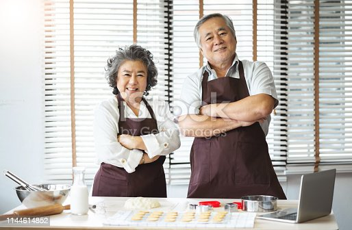 istock Smiling Asian senior couple standing with arms crossed. 1144614852