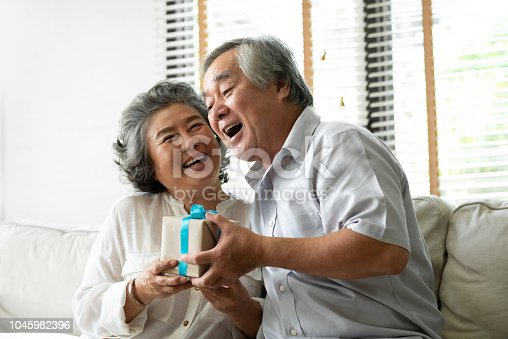 Making a surprise for birthday, Christmas and or year concept. Smiling Asian senior holding gift box together looking each other.