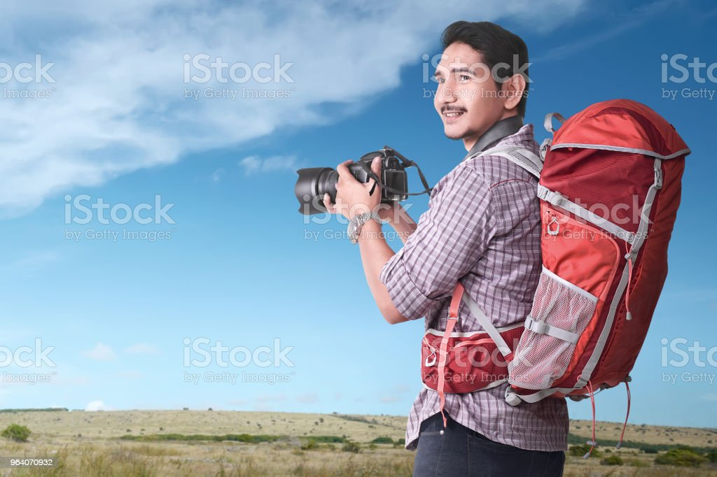 Smiling asian tourist with backpack and camera - Royalty-free Adult Stock Photo