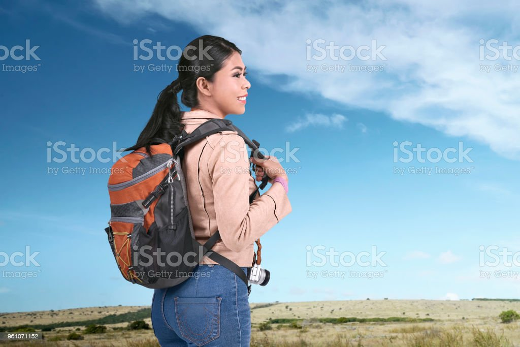 Smiling asian traveler carrying backpack at journey - Royalty-free Adult Stock Photo