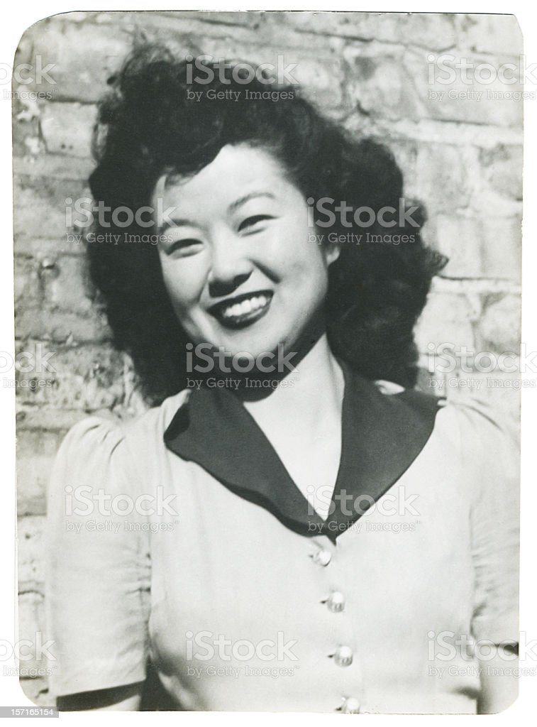 Smiling Asian Woman Against a Brick Wall royalty-free stock photo