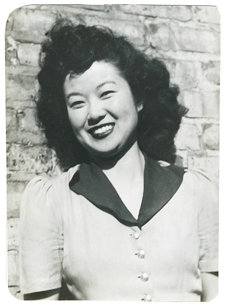 Smiling Asian Woman Against a Brick Wall stock photo
