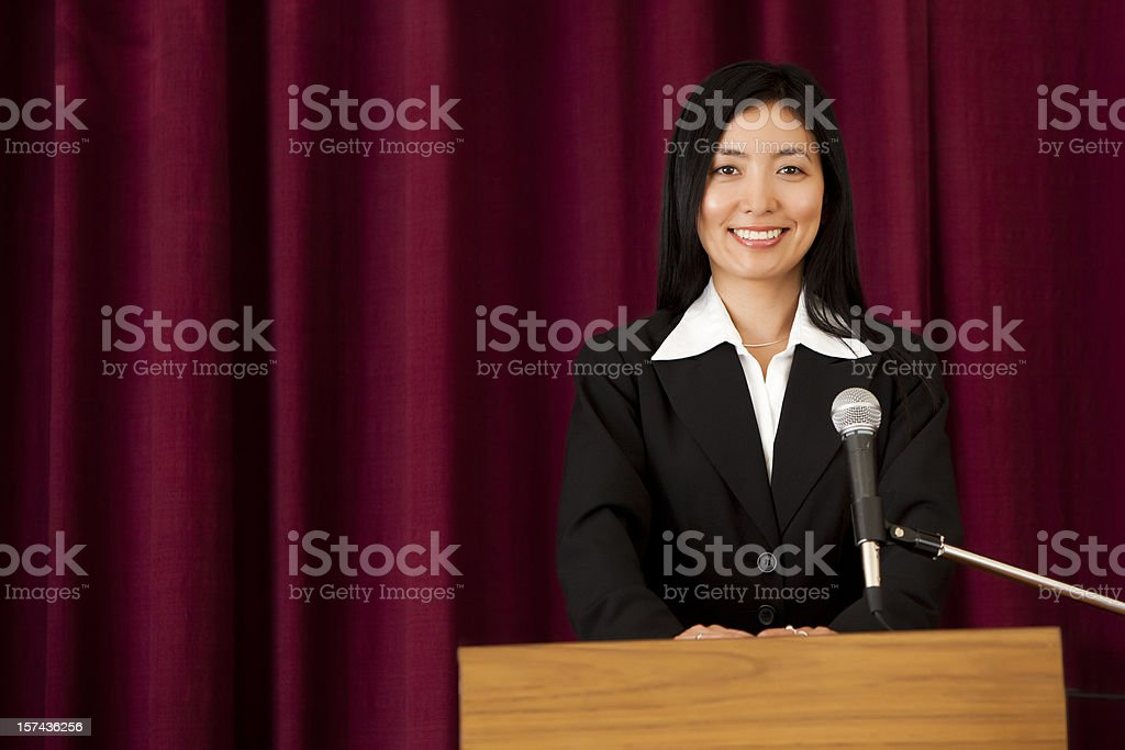 Smiling Asian Woman at Podium stock photo