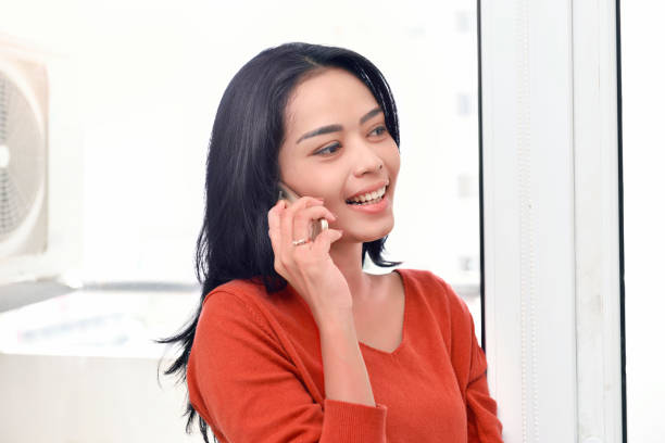 Smiling asian woman making a call Smiling asian woman making a call against window background indonesian ethnicity stock pictures, royalty-free photos & images
