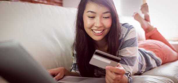 lächelnde asiatische frau auf couch mit tablet shop online - möbel 24 online stock-fotos und bilder