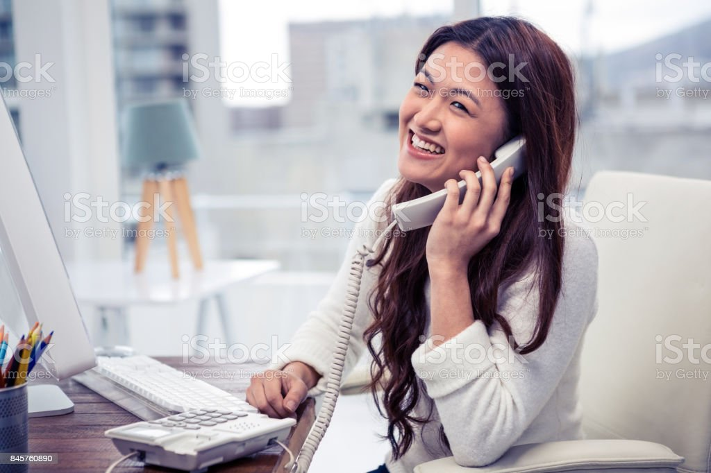 Smiling Asian woman on phone call using computer stock photo