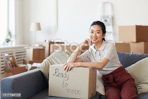 Portrait of young Asian woman smiling at camera while leaning on cardboard box with ready to move inscription, copy space