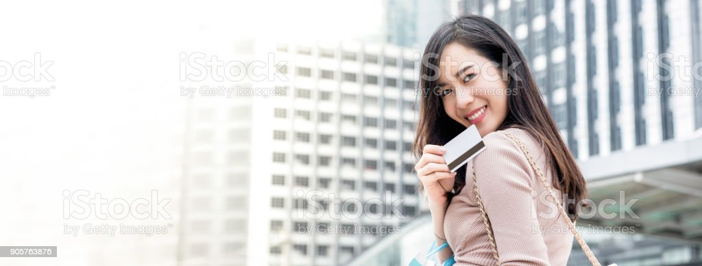 Smiling Asian woman showing credit card stock photo
