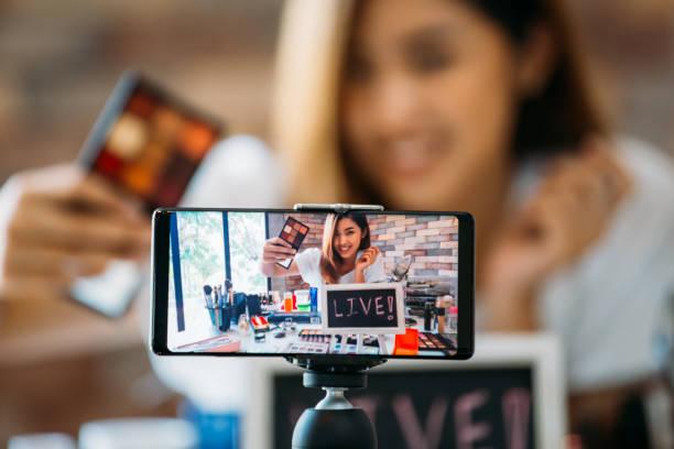 Lächelnde asiatische Frau zeigt Augen auf Display des Smartphones – Foto