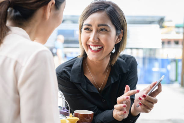 Smiling asian woman showing friend social media on smartphone Indonesian businesswoman and colleague on tea break southeast asian ethnicity stock pictures, royalty-free photos & images