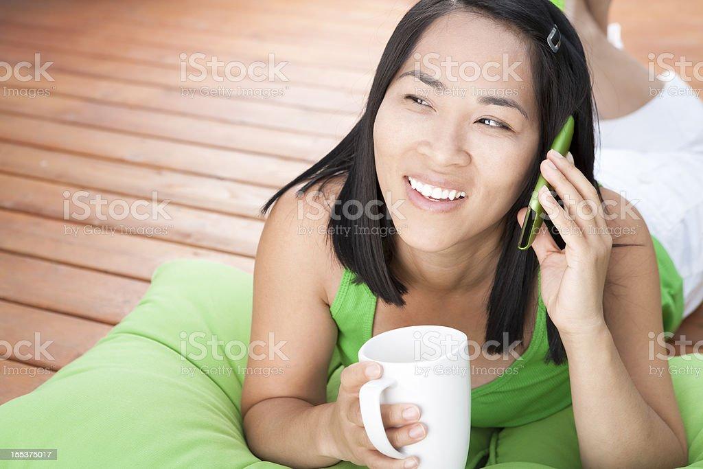 Smiling asian woman talking on cellphone outdoor royalty-free stock photo