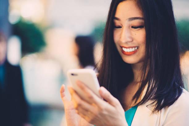 街の中で笑顔アジアの女性のテキスト - スマホ 女性 ストックフォトと画像