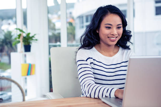 smiling asian woman using laptop - job search stock photos and pictures