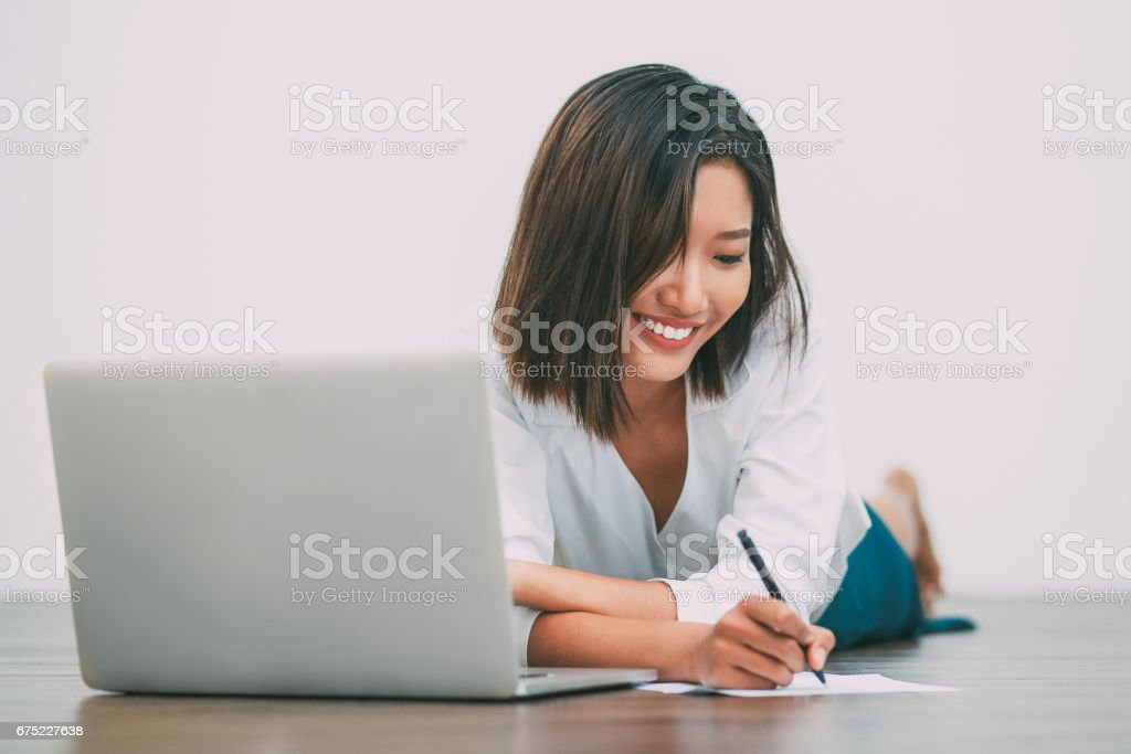 Smiling Asian Woman Writing on Floor with Laptop royalty-free stock photo