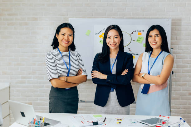 Smiling Asian young business women in casual wear standing in line with arms folded in meeting room stock photo