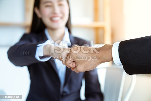 Smiling Asian young businesswoman bump fists with her boss after work success together at an office.Teamwork successful concept