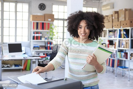 istock Smiling assistant using copy machine at work 693746036