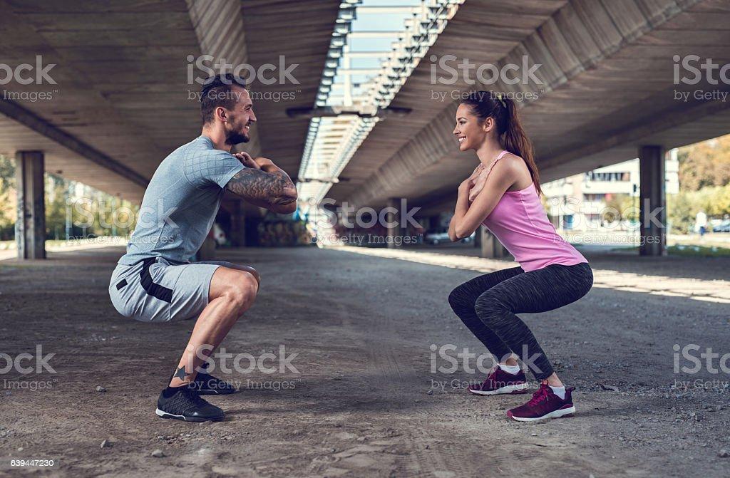 Smiling athletes exercising endurance in a squat position. - foto de acervo