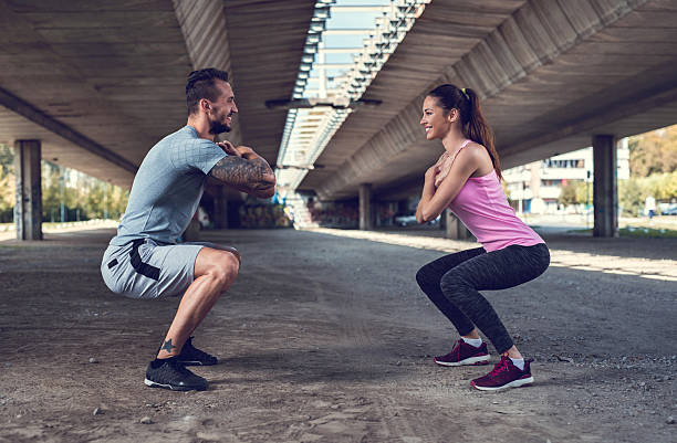 Smiling athletes exercising endurance in a squat position. - foto de acervo