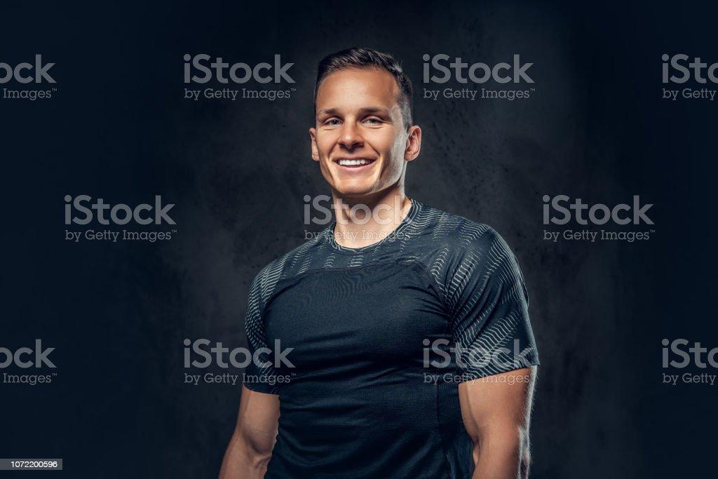 Smiling athletic man on black background - Zbiór zdjęć royalty-free (Aktywny tryb życia)