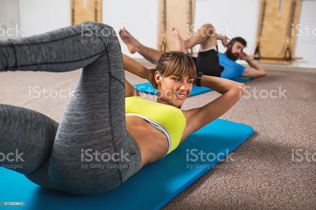 Young woman practicing in health club and doing sit-ups with hand...