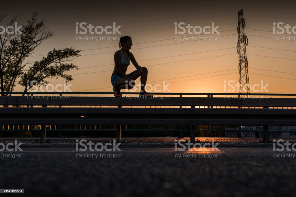 Smiling athletic woman relaxing on a road fence at sunset. royalty-free stock photo