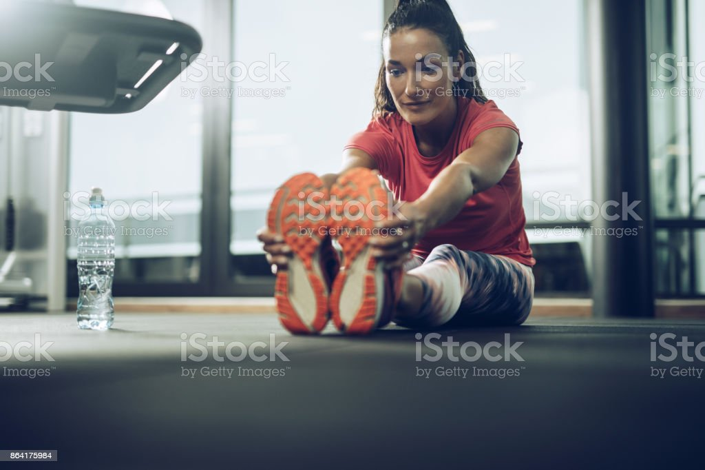 Smiling athletic woman stretching her legs in a gym. royalty-free stock photo