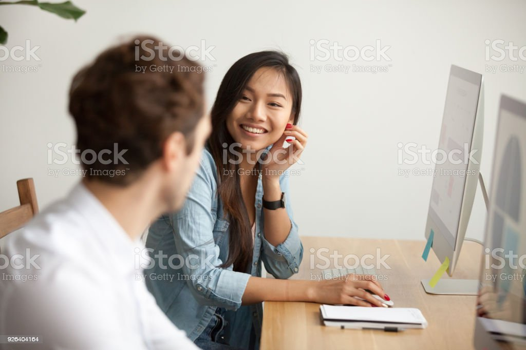Smiling attractive asian woman talking to male colleague at work stock photo