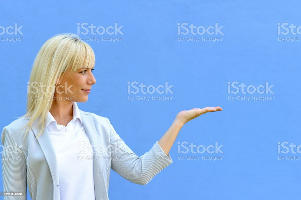 Smiling attractive blond woman holding out a hand - Royalty-free Adult Stock Photo