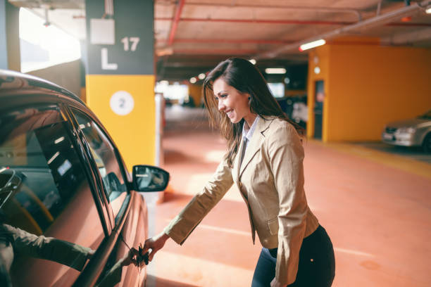 Smiling attractive brunette dressed smart casual opening car door at public garage. Smiling attractive brunette dressed smart casual opening car door at public garage. entering stock pictures, royalty-free photos & images