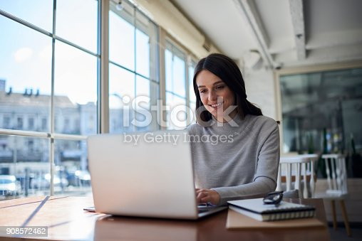 904263506 istock photo Smiling attractive female freelancer doing remote job using laptop computer 908572462