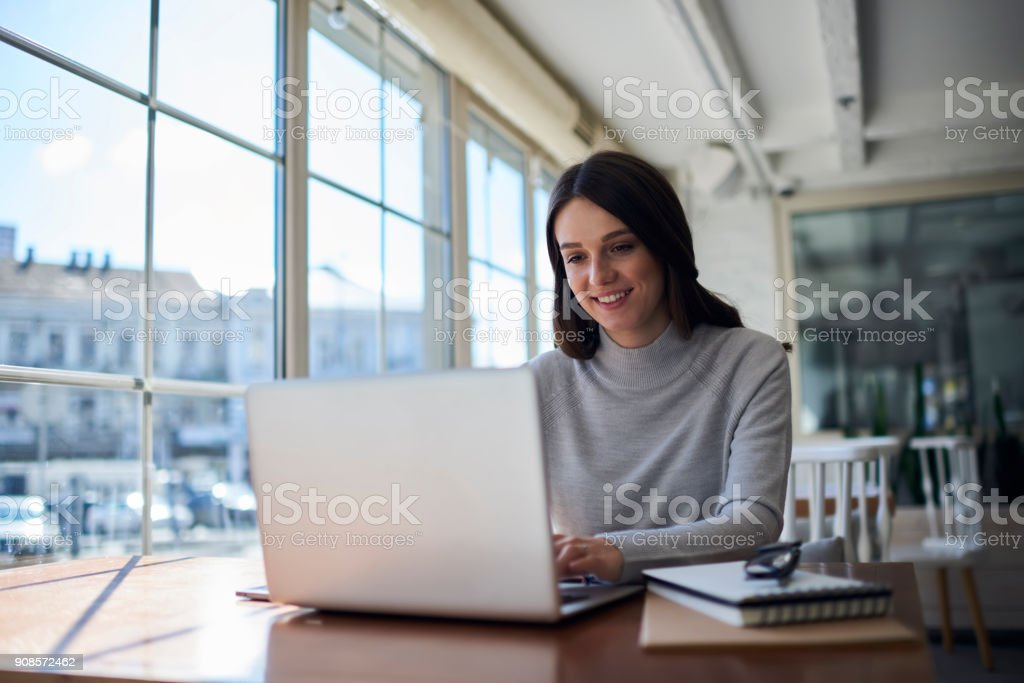Smiling attractive female freelancer doing remote job using laptop computer stock photo