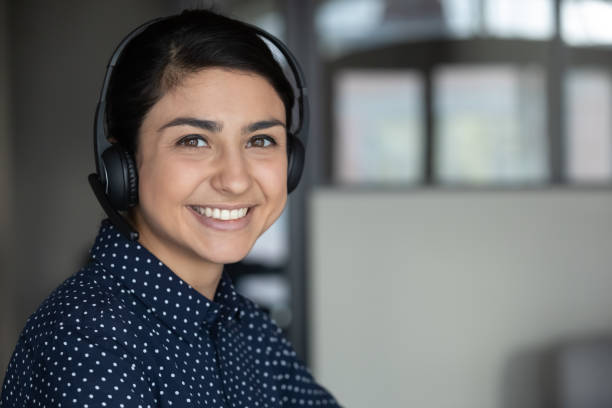 Smiling attractive indian ethnicity millennial businesswoman looking at camera. Head shot close up smiling attractive indian ethnicity millennial businesswoman wearing headphones, looking at camera. Happy sincere pleasant young mixed race female professional working remotely. bingo caller stock pictures, royalty-free photos & images