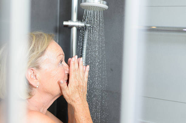 Smiling attractive senior woman taking a shower bildbanksfoto