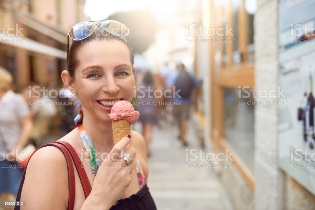 Smiling attractive woman enjoying an ice cream stock photo