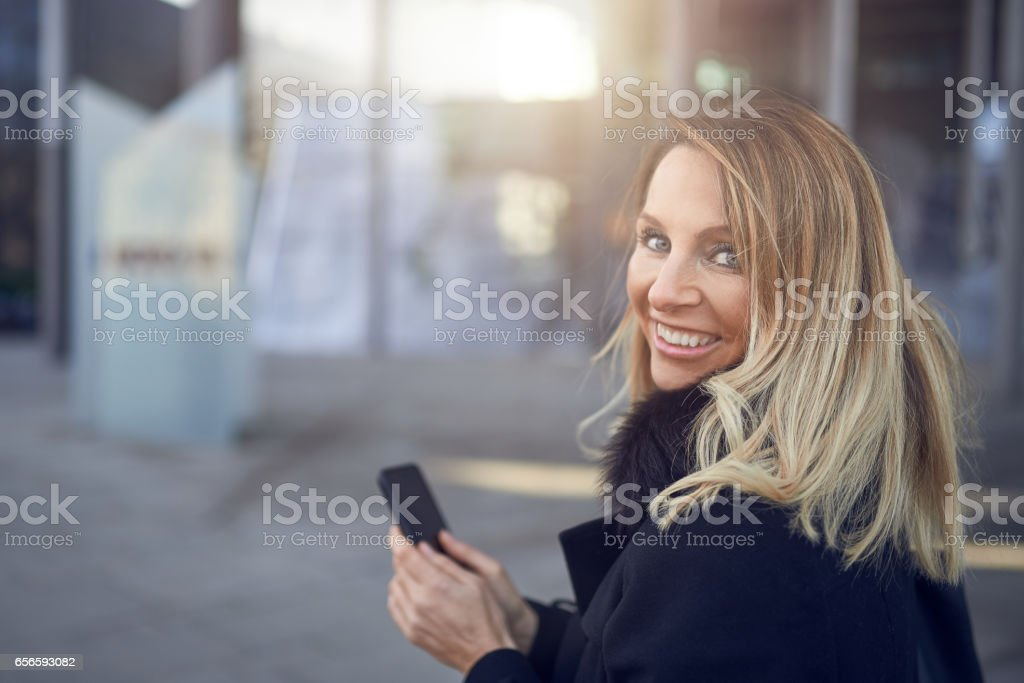 Smiling attractive woman looking over her shoulder stock photo