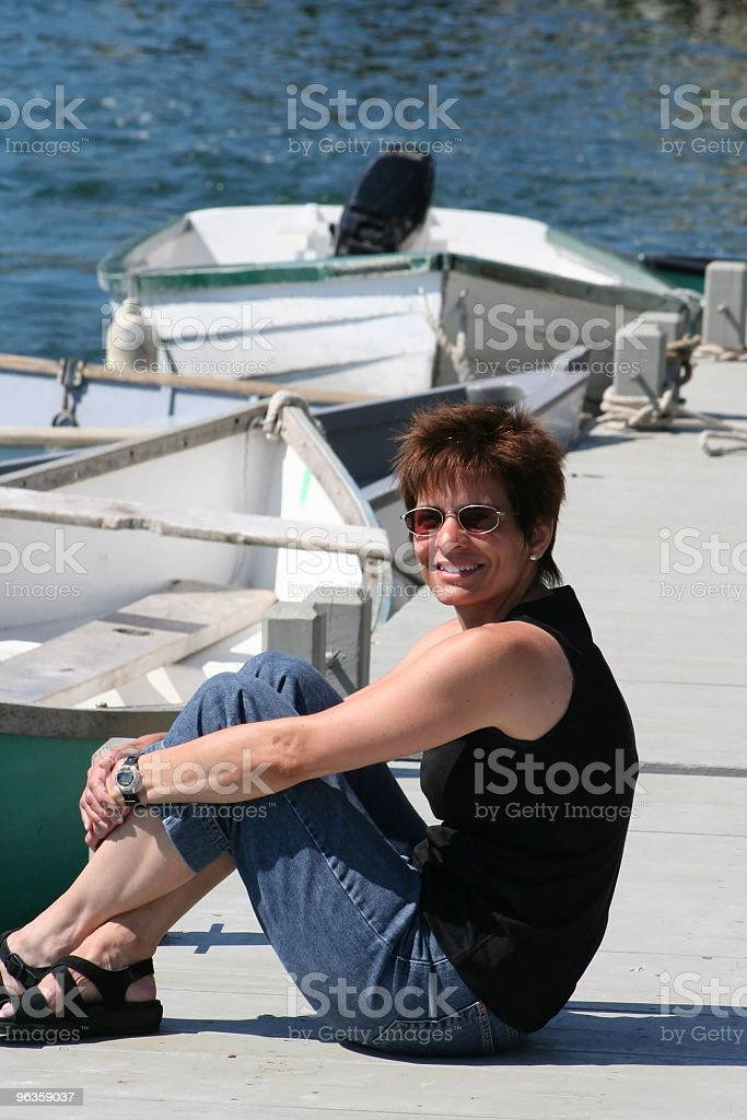 smiling attractive woman sitting on dock stock photo
