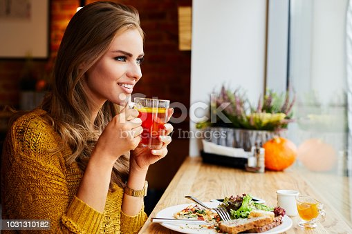 Smiling attractive young lady looking through window while drinking tea sitting in cafe