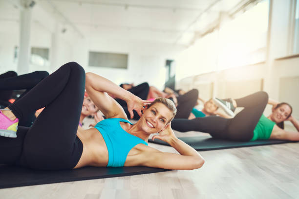 smiling attractive young woman doing aerobics - aerobics stock photos and pictures