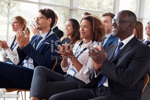 862718922 istock photo Smiling audience applauding at a business seminar 862718334