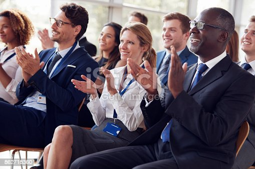 862718922 istock photo Smiling audience applauding at a business seminar 862718360
