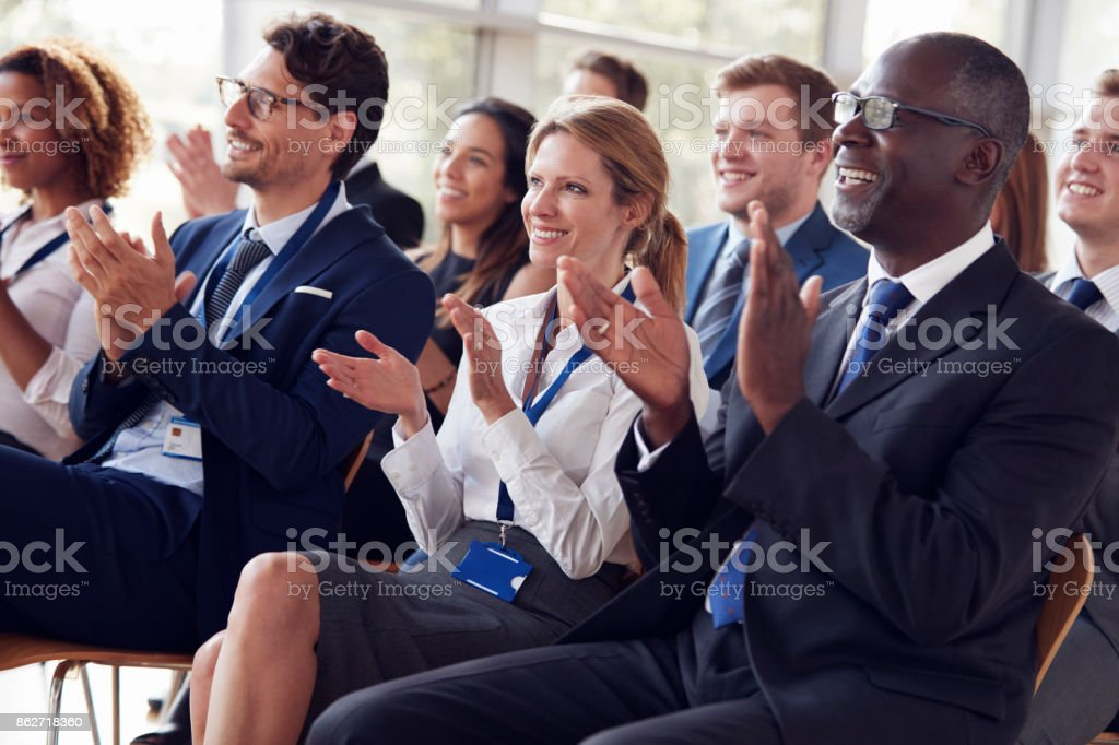 Smiling audience applauding at a business seminar stock photo