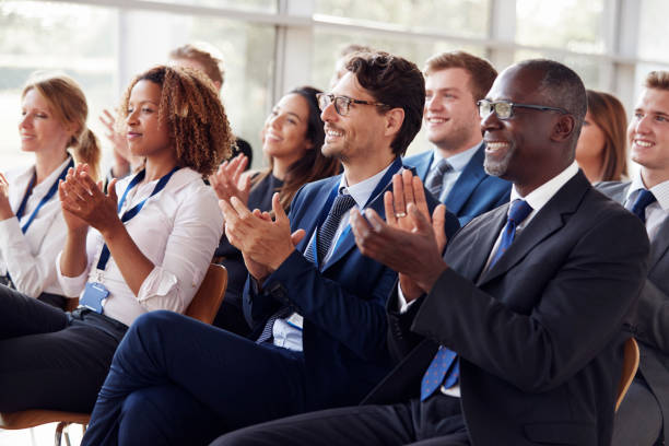 smiling audience applauding at a business seminar - audience clapping stock photos and pictures