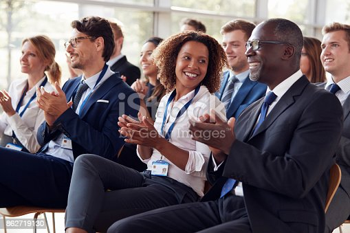 862718922 istock photo Smiling audience applauding at a business seminar 862719130