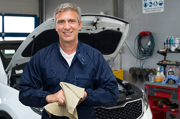 Smiling Auto Mechanic Portrait Of A Happy Auto Mechanic Cleaning Hands With Cloth auto mechanic stock pictures, royalty-free photos & images