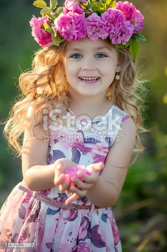 Smiling baby 3-4 year old standing with basket of flowers outdoors. Looking at camera. Summer season