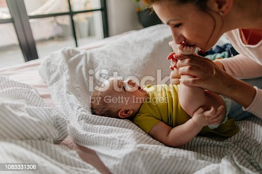 Portrait of a little smiling baby boy and his mom, kissing his tiny feet right after waking up in his nursery