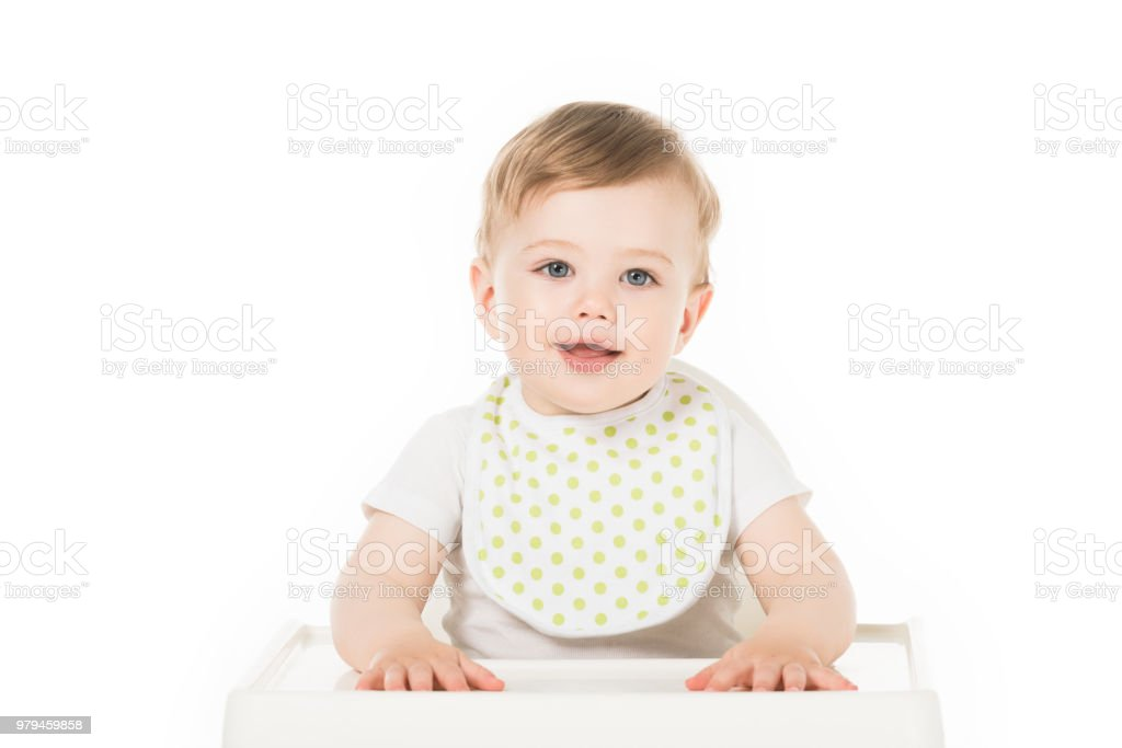 smiling baby boy in bib sitting in highchair isolated on white background stock photo