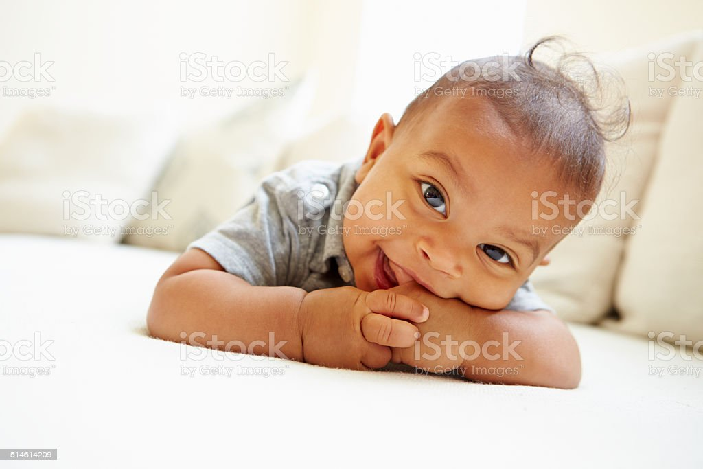 Smiling Baby Boy Lying On Tummy At Home stock photo
